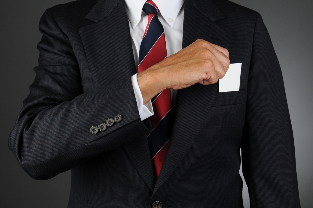 Closeup of a businessman reaching into his breast pocket to-web -  Translation services