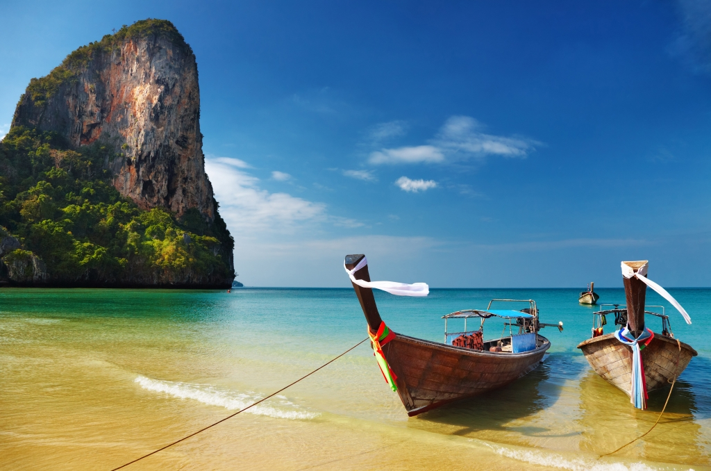 Thai Translation Services. Tropical beach, traditional long tail boats- Thailand