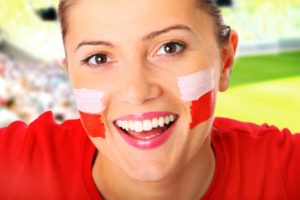Polish Translation Services happy Polish female fan cheering with stadium background