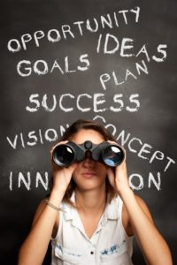 women looking through binoculars in front of a white board with motivating words on-web