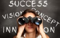 women-looking-through-binoculars-in-front-of-a-white-board-with-motivating-words